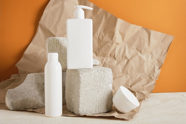 Контейнеры для мыла и крема на бетонных подиумах. упаковка косметики для ухода за кожей. косметический