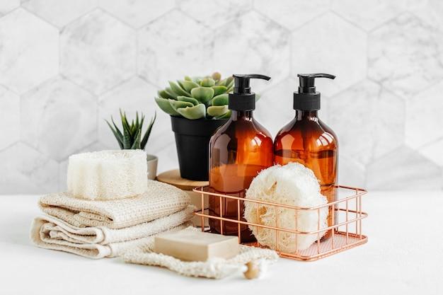 石鹸とシャンプーのボトルと綿のタオル、バスルームの背景の白いテーブルに緑の植物。