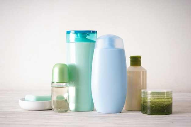 Бутылки для мыла и шампуня. различные косметические бутылки на деревянных фоне.