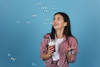Soap balloons fly around a happy girl drinking milk shake and dancing with the earphones