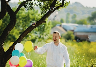 Soap balloons fly around a man standing under green tree
