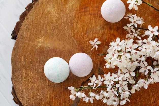 Мыльный баннер. ароматическое натуральное мыло и бомба для ванны с цветами сакуры на деревянном фоне, вид сверху