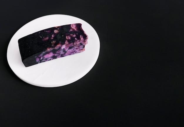 Soap bar on circular white board over black backdrop