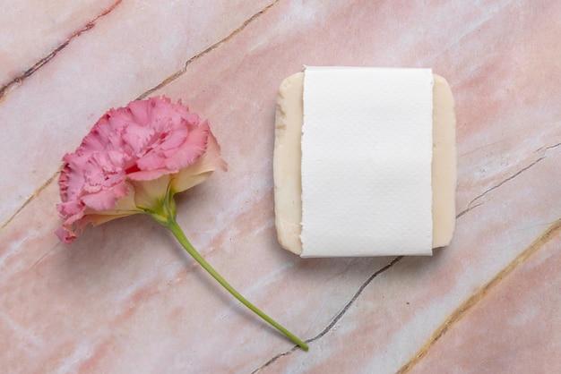 분홍색 꽃이 있는 대리석 테이블에 누워 있는 비누 바, 위쪽 전망. 비누 모형