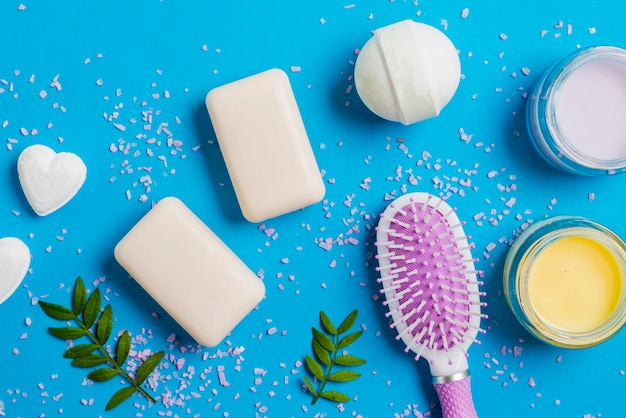 Soap; bath bomb; moisturizer cream and hairbrush on blue background