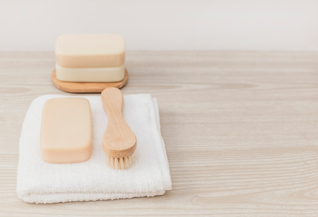 Soap; brush and towel on wooden tabletop
