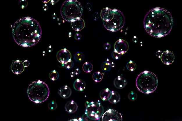 Soap bubbles rainbow floating in darkness.
