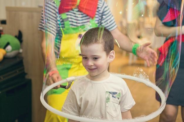 비눗방울은 어린이 파티에서 광대를 보여줍니다. 광대는 어린이 이벤트를 위해 쇼를 개최합니다.