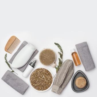 Soap, cotton grey towel, branch of eucalyptus, washcloth for bath, wooden hairbrush.