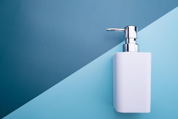 Soap dispenser isolated on blue