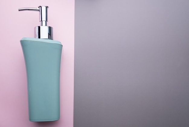 Soap dispenser isolated on pink