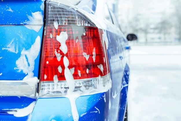 Soap foam drips down the glass. self-service car wash