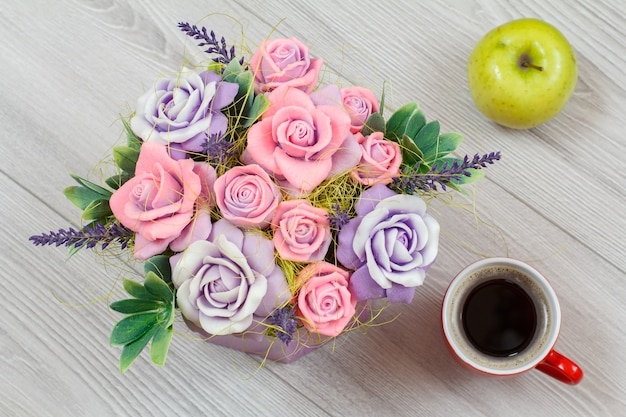Soap in form of colorful various flowers, an apple and a cup of coffee on the gray wooden surface
