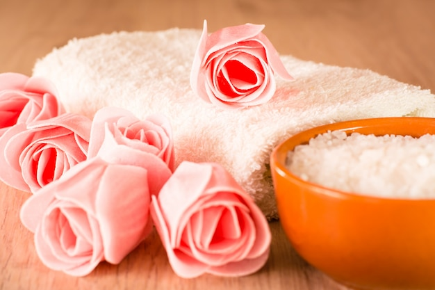 Soap in the form of flowers, sea salt in the bowl and towel on a wooden background