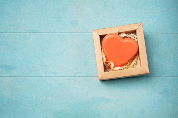 Soap in the form of a heart in a gift box on a blue surface,