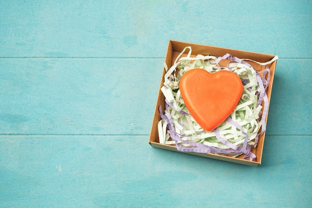 Soap in the form of a heart in a gift box on blue
