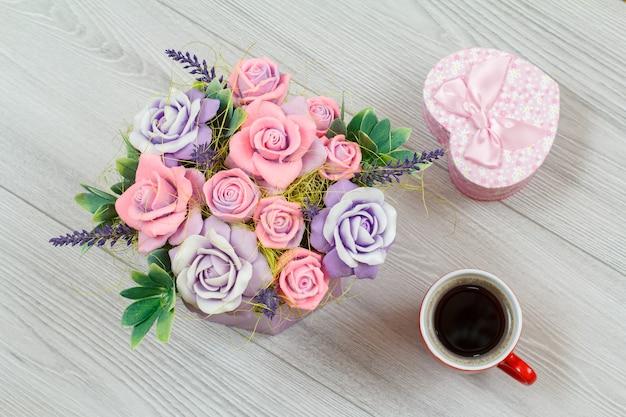회색 나무 배경에 다채로운 꽃 모양의 비누, 선물 상자, 커피 한 잔. 평면도.