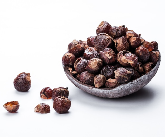 Soap nuts on a white surface in the coconut. care products. natural, organic and