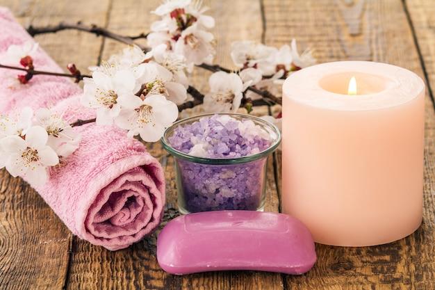 비누, 욕실 절차를 위한 수건과 함께 유리 그릇에 바다 소금, 배경에 살구 나무의 꽃 가지와 함께 불타는 촛불. 스파 제품 및 액세서리