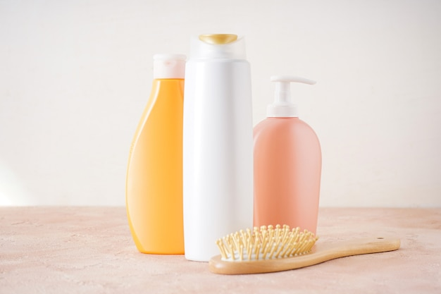 Soap and shampoo bottles and hair brush on beige table inside a bathroom background.