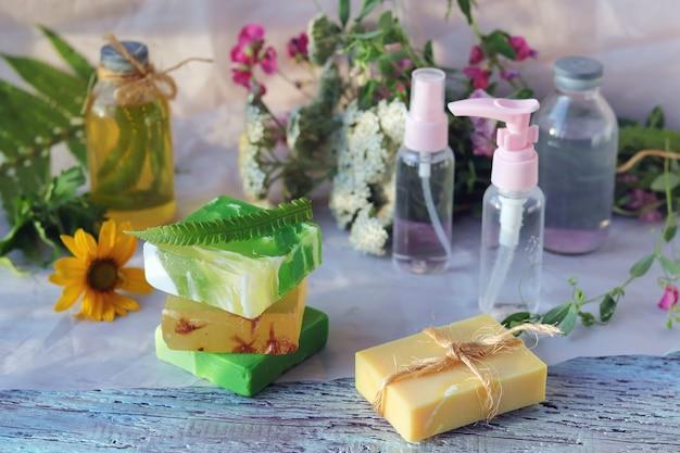 Мыло, спрей, букет лекарственных трав и стеклянные бутылки с ароматическим маслом на деревянном столе