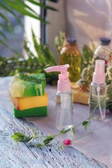 비누, 스프레이, 약초 꽃다발 및 나무 테이블에 아로마 오일이 든 유리 병