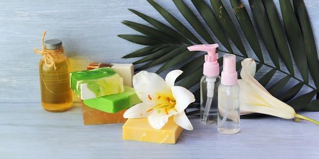 비누, 스프레이, 백합 꽃, 나무 테이블에 아로마 오일이 든 유리 병, 스파, 천연 화장품