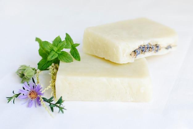 Мыло с цветами лаванды для ухода за кожей на белой поверхности