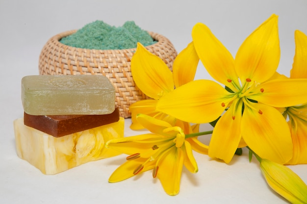 Мыло с натуральными ингредиентами и желтыми цветами лилии на белом фоне
