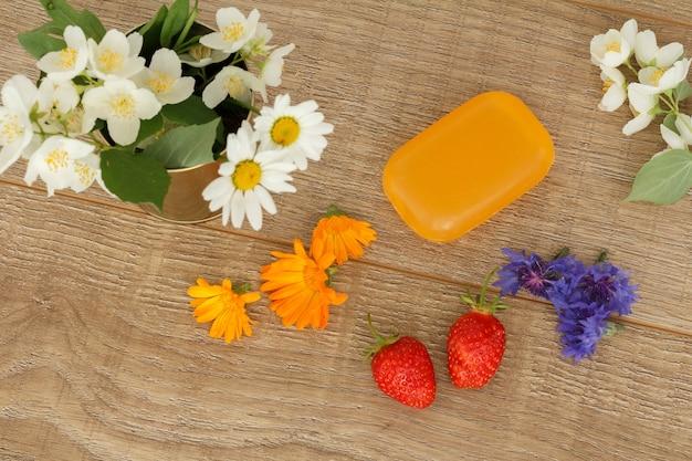나무 데스크탑에 흰색 카모마일 꽃, 노란색 메리골드 꽃, 딸기가 있는 비누. 평면도.