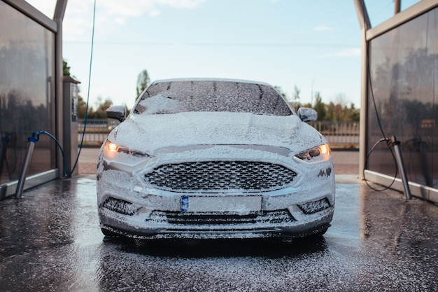 A soapy gray sedan stands at a self-service car wash