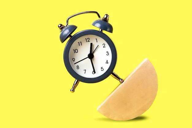 幾何学的図形の一部にとどまる高騰目覚まし時計。人生のさまざまな部分のバランスの概念。現代的なスタイル。
