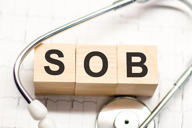 木製のブロックに書かれたすすり泣きの言葉と明るい背景の聴診器。病院、診療所、医療ビジネスの概念的なヘルスケア