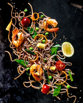 Soba noodles with vegetables and shrimps - asian food creative concept