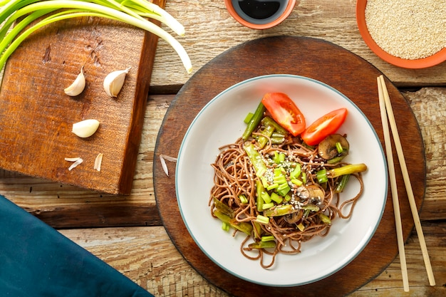 Soba with mushrooms, green beans and sesame seeds in a plate on a stand on a wooden table next to chopsticks and soy sauce and garlic. horizontal photo