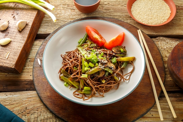 Soba with mushrooms, green beans and sesame seeds in a plate on a stand on a wooden table next to chopsticks and soy sauce and garlic on stands. horizontal photo