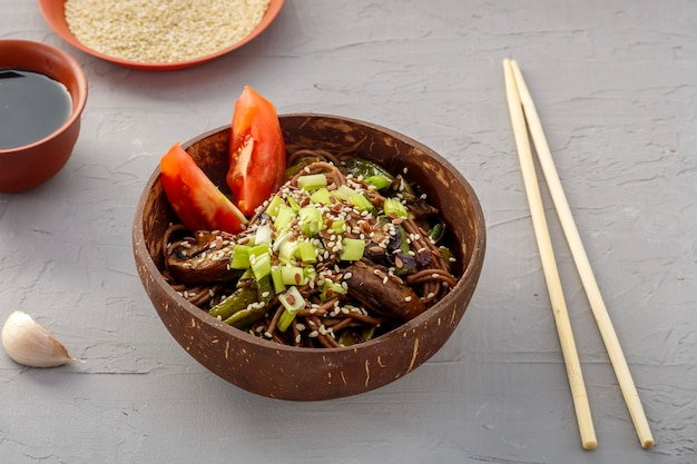 Soba with mushrooms and sesame seeds in a plate of coconut shells on a concrete background near garlic and soy sauce and sticks. horizontal photo