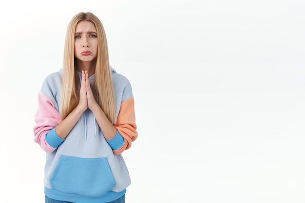 Singhiozzante ragazza carina e cupa che implora aiuto, si tiene per mano in preghiera, fa una smorfia e si acciglia triste, ha bisogno di consigli