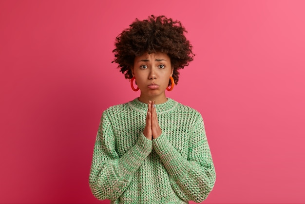 すすり泣く不機嫌な巻き毛の女性は暗い表情で見え、祈りの手を握り、謝罪、助けまたは恩恵を求め、ひどく何かを必要とし、ニットのジャンパーを着て、困難な状況で立ち往生