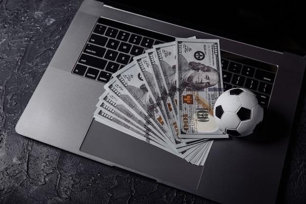 キーボードのサッカーボールとドル紙幣。スポーツ、ギャンブル、賭けの概念。