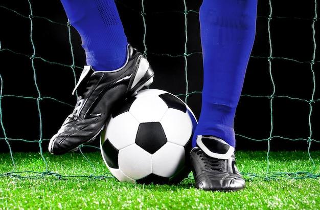 Футбольный мяч и ноги на футбольном поле, футболист в синих леггинсах