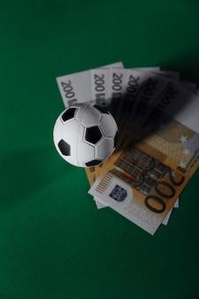 サッカーボールとお金。スポーツ、ギャンブル、お金の勝利の概念。垂直方向の画像。