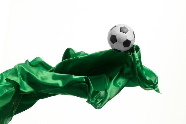 サッカーボールと白いスタジオ背景に分離または区切られた滑らかなエレガントな透明な緑の布。