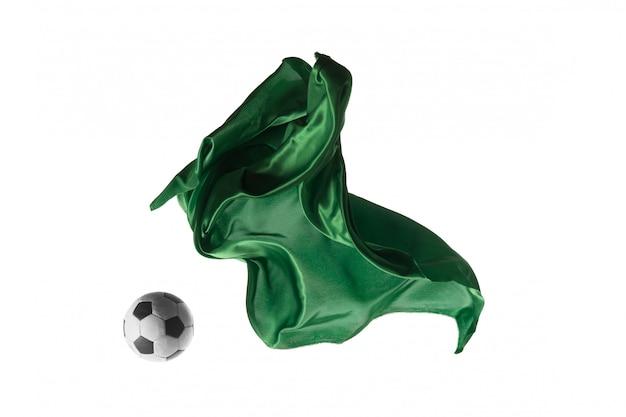 Футбольный мяч и гладкая элегантная прозрачная зеленая ткань, изолированные или разделенные на белом