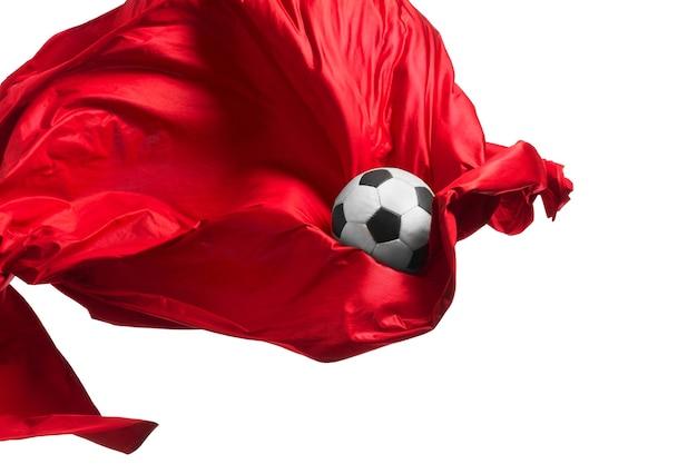 축구공과 부드럽고 우아한 투명한 붉은 천은 흰색 스튜디오 배경에서 분리되거나 분리됩니다.