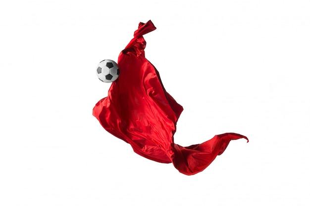 Футбольный мяч и гладкая элегантная прозрачная красная ткань или разделены на белой студии.