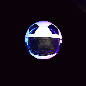 A soccer ball in a black medical mask from the virus. in the light of neon on a dark wall