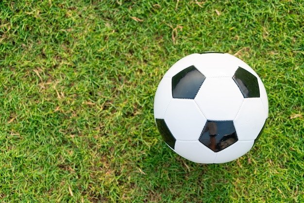 Soccer ball on the football field  background with copy space