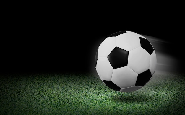 Soccer ball on green grass and black background
