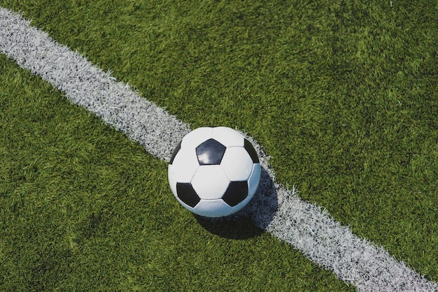 Soccer ball on green grass over the white line